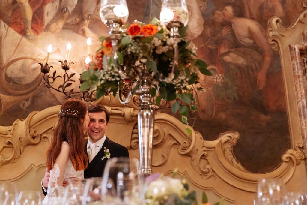 La sposa seduta sulle gambe dello sposo lo bacia sulla guancia mentre ride