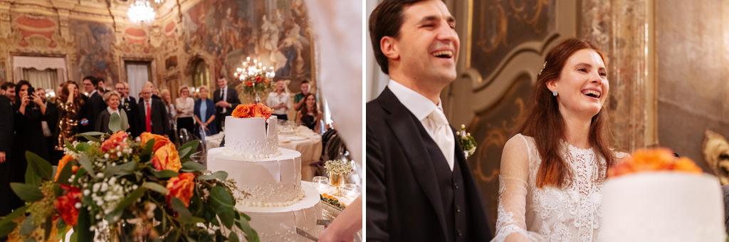 Gli sposi ridono con gli invitati dopo il taglio della torta