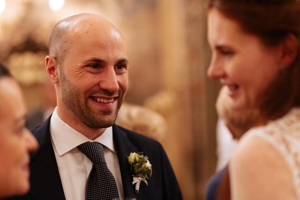 Il fratello dello sposo sorride parlando con la sposa