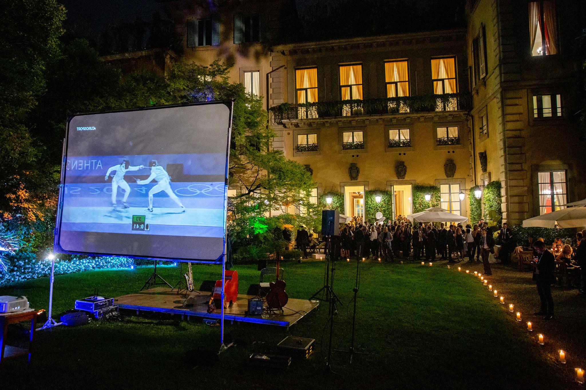 La sfida di scherma con Valentina Vezzali è proiettata sullo schermo del cortile della Società del Giardino